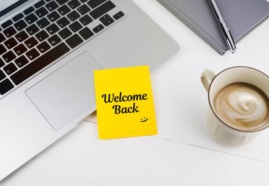 Welcome back note with notebook, pen and coffee